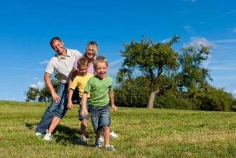 11193707-familia-feliz-con-dos-ninos-jugando-en-la-hierba-en-un-prado-de-verano